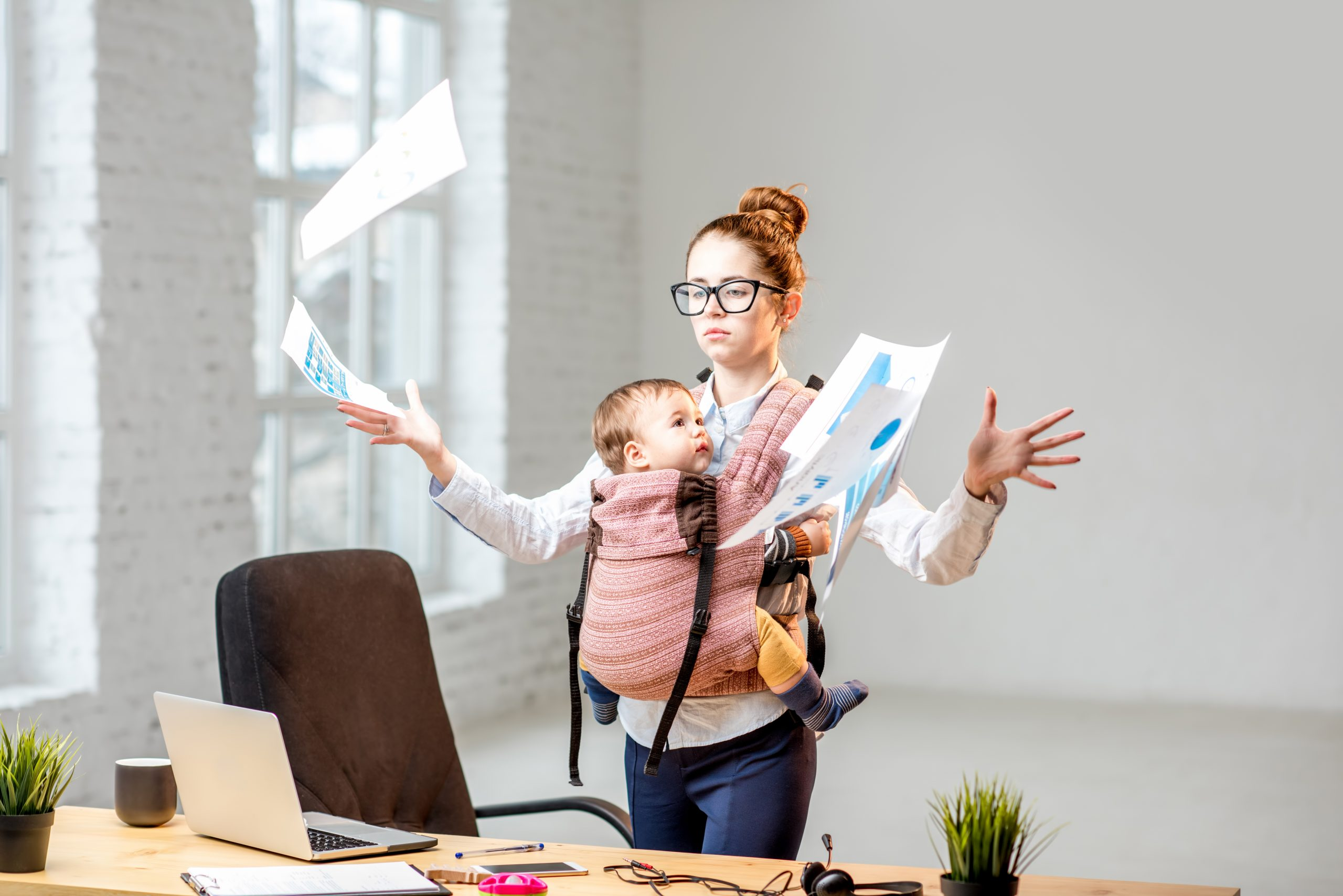 Multitasking and exhausted businesswoman throwing up a documents standing with her baby son during the work at the office