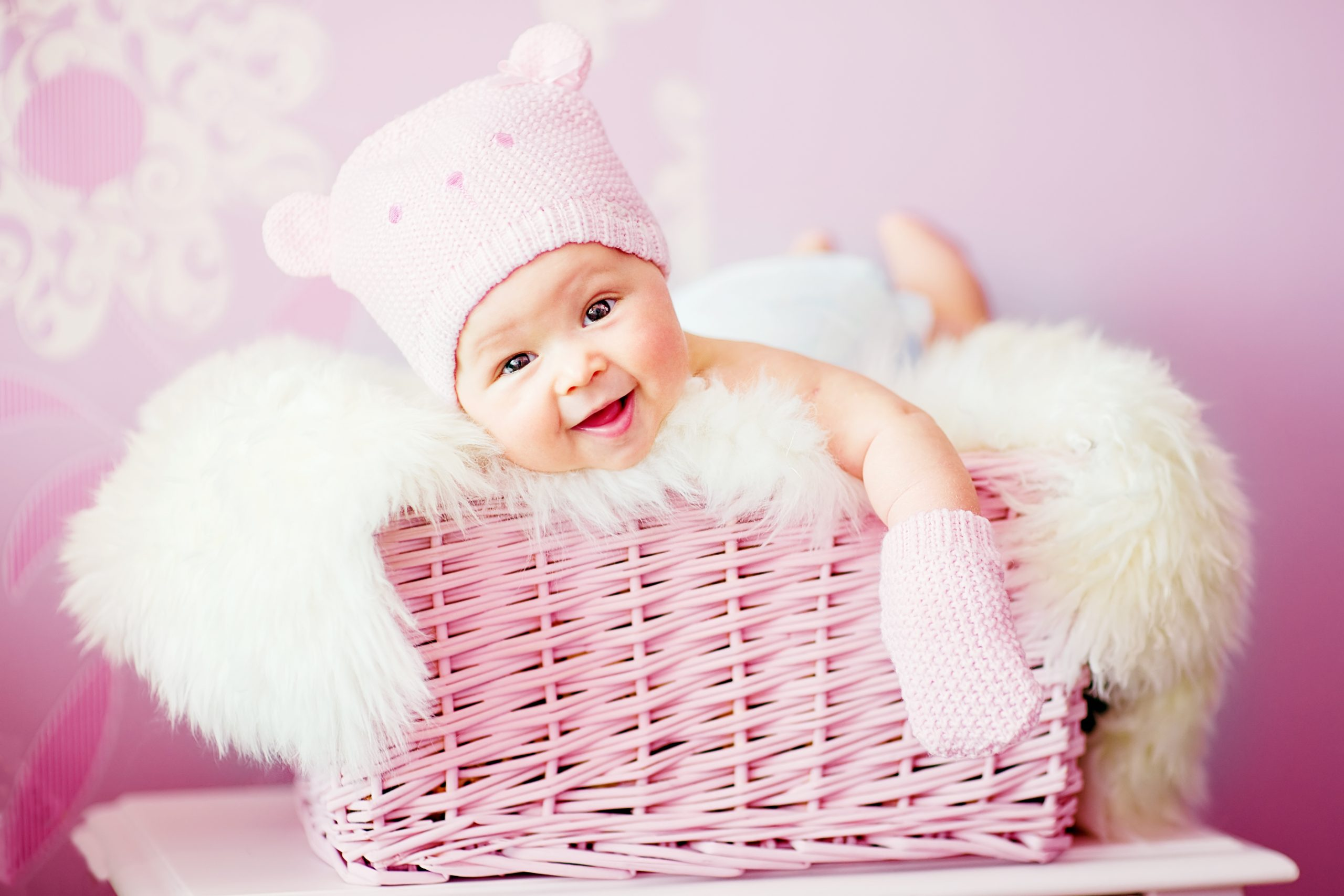 baby girl in pink knitted bear hat lies at basket